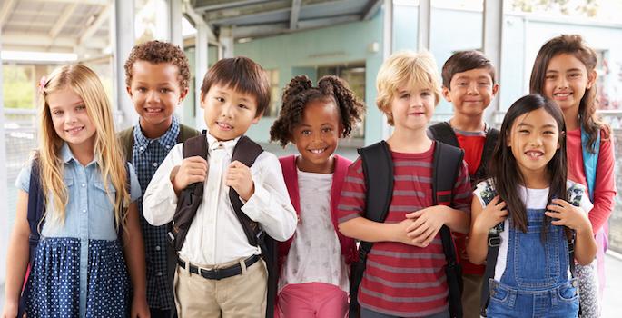 Group portrait of diverse elementary school kids in school corridor