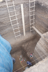 Excavation pit several stories deep with ladders and workers