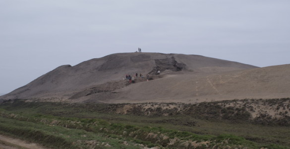distance view of temple mound with tiny people atop it for scale