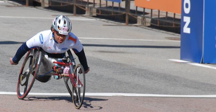 Anjali in wheelchair crossing finish line at marathon