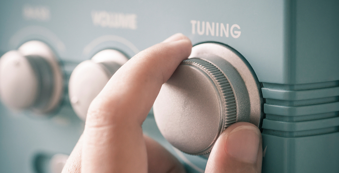 hand on radio tuning knob