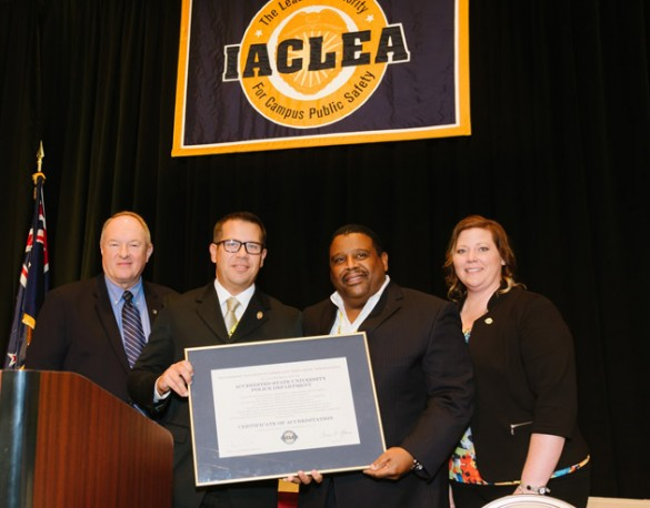 Assistant Chief Rick Burr (second from left) and Chief August Washington (second from right) accept VUPD's reaccreditation certificate at the IACLEA conference.
