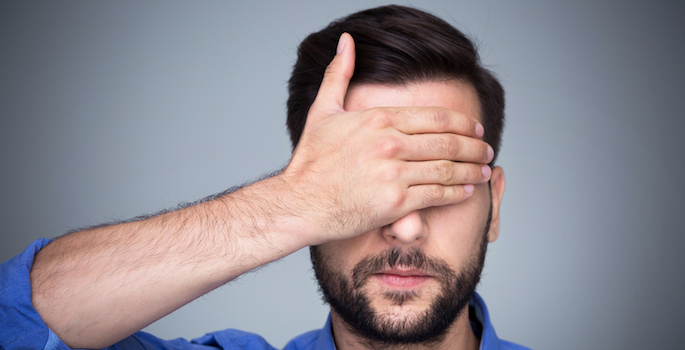 man with hand over his eyes