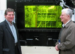 researchers standing outside an illuminated control room
