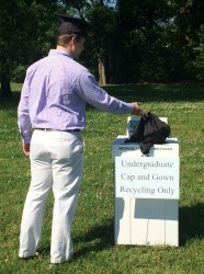 A 2016 graduate drops his recyclable gown into a collection box after Commencement.