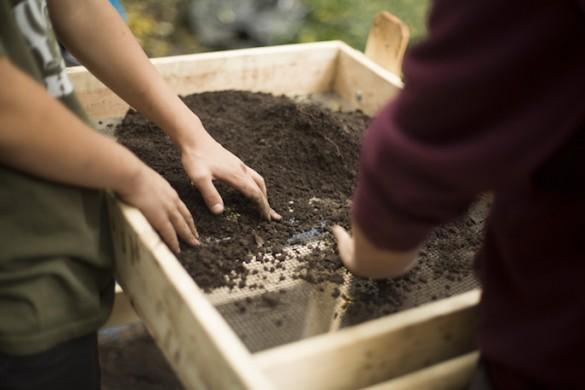 close-up of hands sifting dirt through mesh