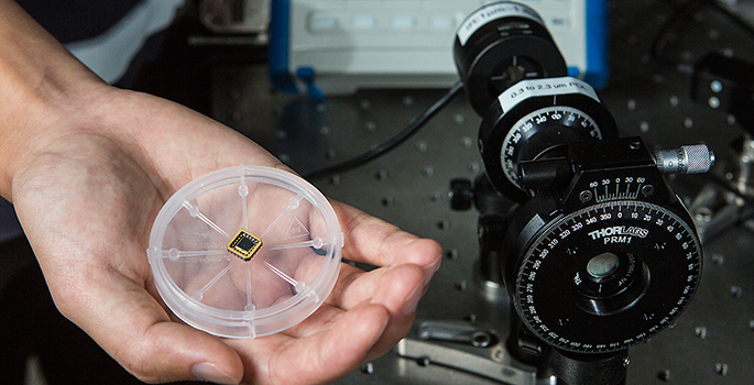 hand holding petri dish containing microchip next to large scope device