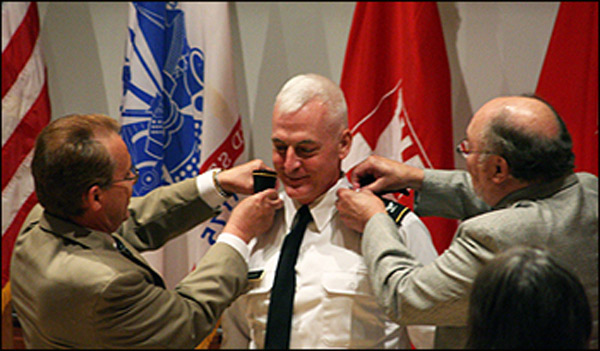 Dean Philippe Fauchet (left) and former Dean Kenneth F. Galloway remove Col. LeBoeuf's shoulder boards and replace them with the brigadier general's one-star shoulder boards.