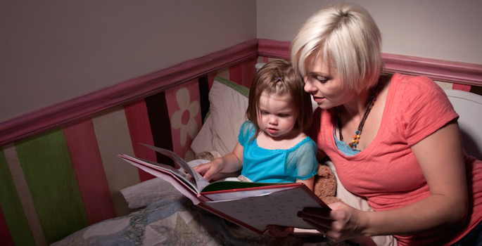 mom reading bedtime story to toddler girl
