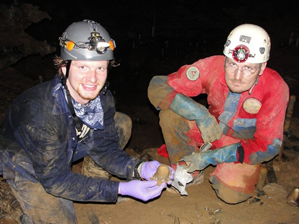 researchers underground wearing hard hats holding rock samples
