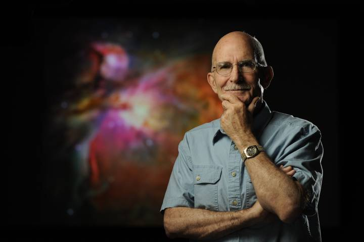 Bob O'Dell standing in front of image of Orion Nebula