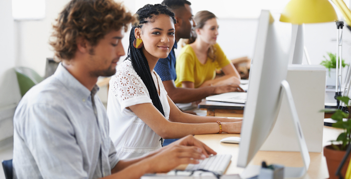 diverse young adults working at computers