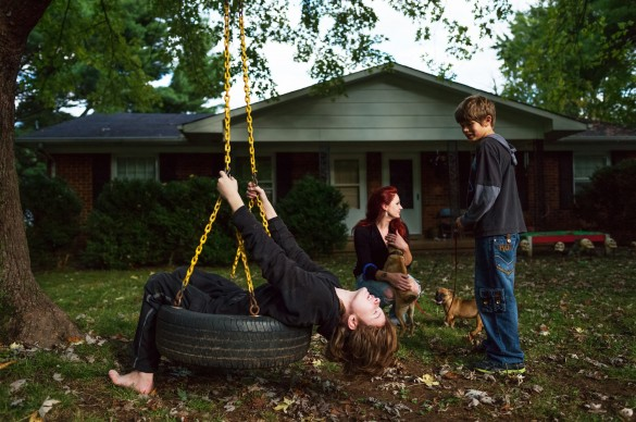Woman on tire swing with children looking on in front of house