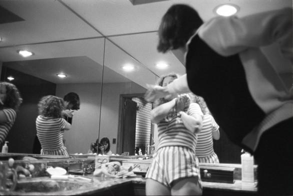 Man striking woman in front of mirror