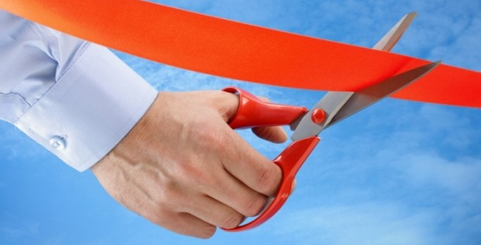 concept of scissors cutting red ribbon
