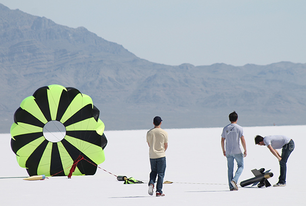 Students view rocket lying on the ground with parachute fluttering.