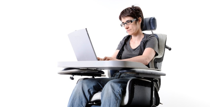woman using electric wheelchair and computer