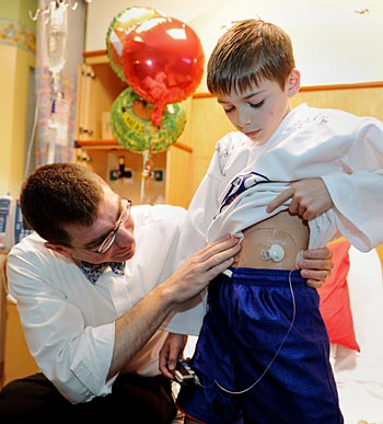 Drew Bremer, M.D., Ph.D., examines the new insulin pump and monitor recently placed on 10-year-old Jackson Sevelius' abdomen for a new type 1 diabetes study at Vanderbilt. (photo by Joe Howell)