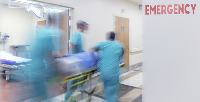 "Three emergency medical workers rushing patient in gurney down hall past sign reading ""Emergency"""