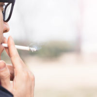 Profile of Asian man in glasses smoking a cigarette