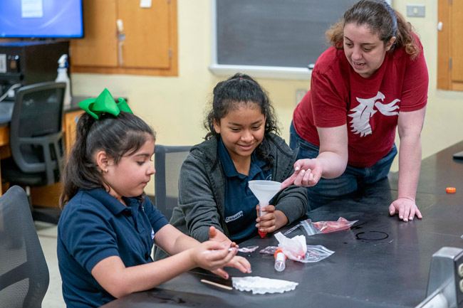 MSTP student Tory Martucci (right) helps middle school students extract DNA from strawberries. (Vanderbilt University)