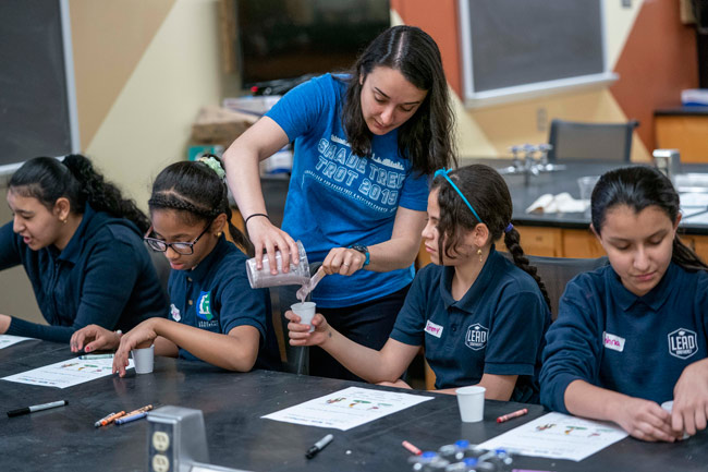 MSTP student Evonne McArthur helps local middle school students create a model of their thumbs as they learn about prosthetics and bionics. (Vanderbilt University)