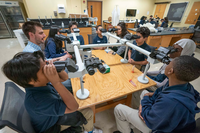 The students look at microbes under the microscope with MSTP student Matt Madden. (Vanderbilt University)