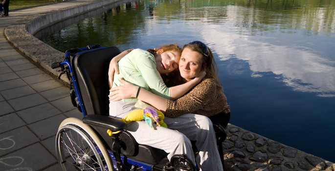 Woman hugging a girl in a wheelchair