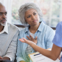 female physician explaining something to elderly african american couple in doctors office