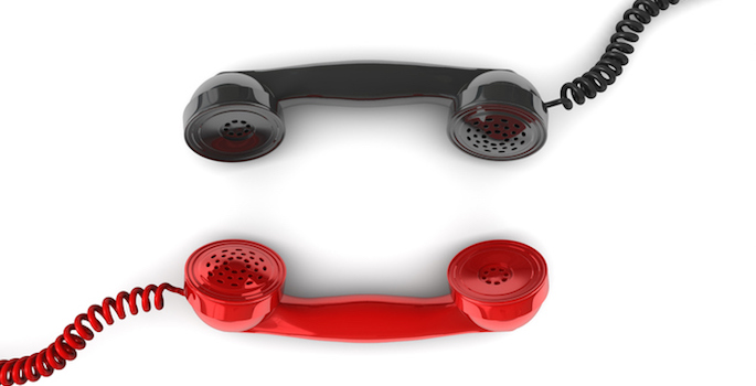 Red telephone handset facing black telephone handset conceptualizing communication between the two