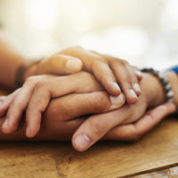 Close up of a person's hand being clasped in a comforting manner between the hands of another person.