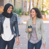 Two women of middle eastern descent, one wearing hijab, strolling down the sidewalk deep in conversation.