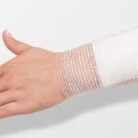 large gauze pad held in place on an arm by an elastic gauze bandage