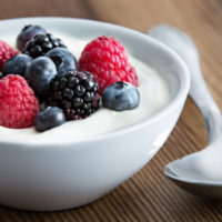 Bowl of fresh mixed berries and yogurt with farm fresh strawberries, blackberries and blueberries served on a wooden table (Bowl of fresh mixed berries and yogurt with farm fresh strawberries, blackberries and blueberries served on a wooden table