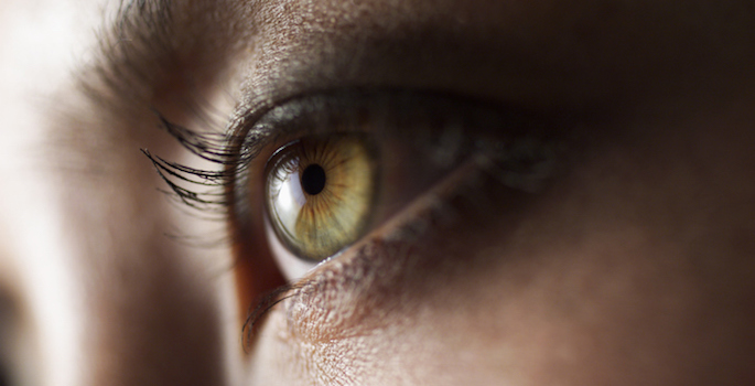 close up of medium skin toned woman's eye with hazel colored iris