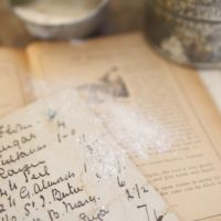 old recipe atop a cookbook from 1894 dusted with flour with vintage sifter and measuring cup in background (Getty)