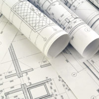 Photo of rolled-up blueprints on drafting desk