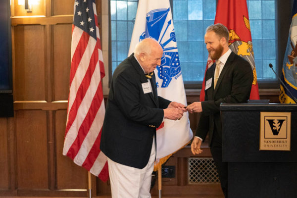 Vanderbilt alumnus and longtime administrator John S. Beasley II (left) receives a Bass Military Scholar challenge coin from inaugural Beasley Scholarship recipient Matthew Smith, a School of Medicine student and former Navy SEAL. (Joe Howell/Vanderbilt)