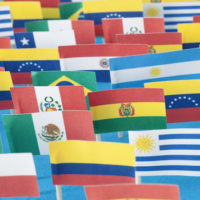 Lots of small handmade flags of latin american countries over blue background