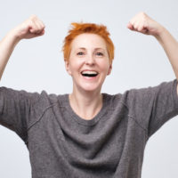 Cheerful mature woman with red short hair smiling with raised fists showing her strength and positive mood. I am the winner concept (Cheerful mature woman with red short hair smiling with raised fists showing her strength and positive mood. I am the w
