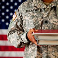 Military person holding books