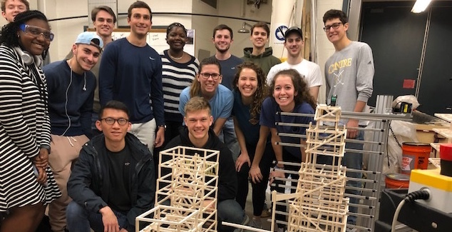 Civil engineering students pose behind a project where they built and tested balsa wood towers