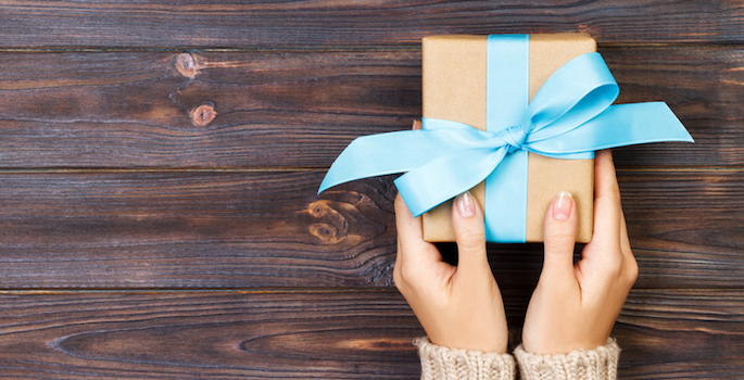 caucasian woman's hands holding a small gift wrapped in brown paper with a blue bow against a dark wood paneled background