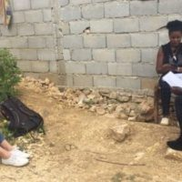 Young caucasian woman sits on the ground facing a black male survey taker and a black woman sitting on a chair outside a cinderblock house