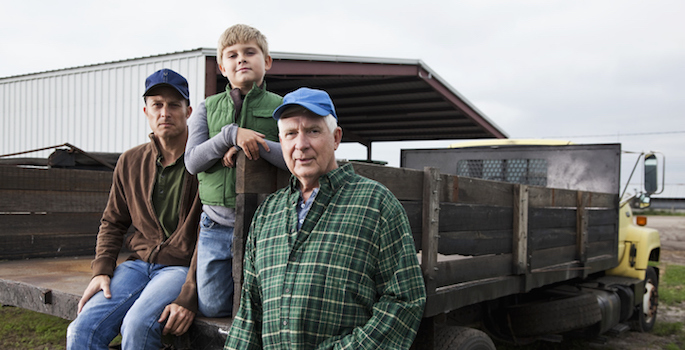 Three generations of men at the back of a truck on the family farm. The grandfather, a senior man in his 60s, is standing with his hand in his pocket, looking at the camera. His adult son and young grandson are behind him on the truck. They are wearing jeans, work boots and jackets or flannel shirt. Everything is brown or green, earthy colors.