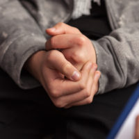 Young teenager boy uncomfortable at counseling - close up on clutching hands