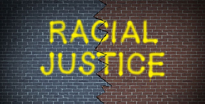brick wall with 'racial justice' spray painted in yellow over a thick crack bisecting the middle of the wall