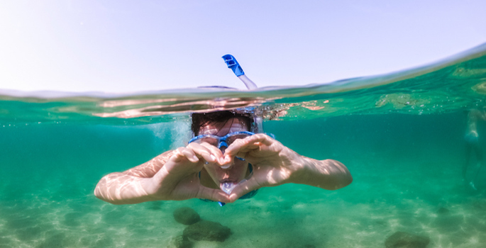 head-on underwater photo of caucasian male snorkeling and making heart shape with hands