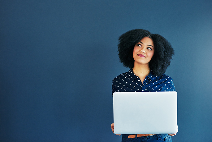 Woman with laptop looks upward, considering her options.