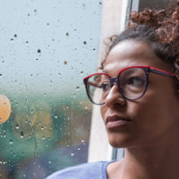 Sad african american woman looking out of the window on rainy weather